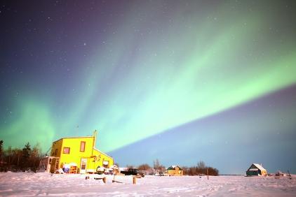 La maison jaune en dessous des aurores boréales à Yellowknife (Territoires du Nord Ouest, Canada) ©Bertrand Lemeunier