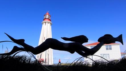 """Phare du site historique maritime de la Pointe-au-Père avec la sculpture """"La grande nageuse"""" une oeuvre de l'artiste Roger Langevin, (Rimouski, Québec, Canada) ©Bertrand Lemeunier"""