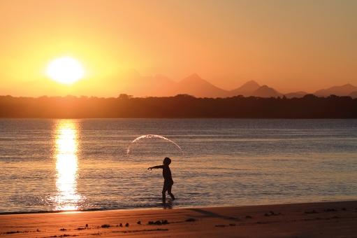 """Enfant jouant dans l'eau au coucher du soleil à """"Barra do Superagui"""" (Parana, Brésil) ©Bertrand Lemeunier"""